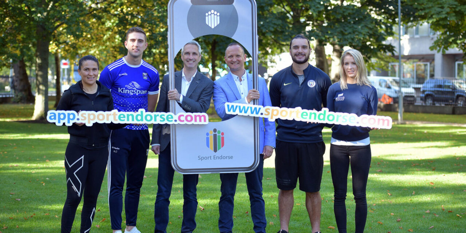 Sport Endorse founders Declan Bourke and Trevor Twamley PR shot with 4 athletes holding giant mobile phone and online URL promotional banners